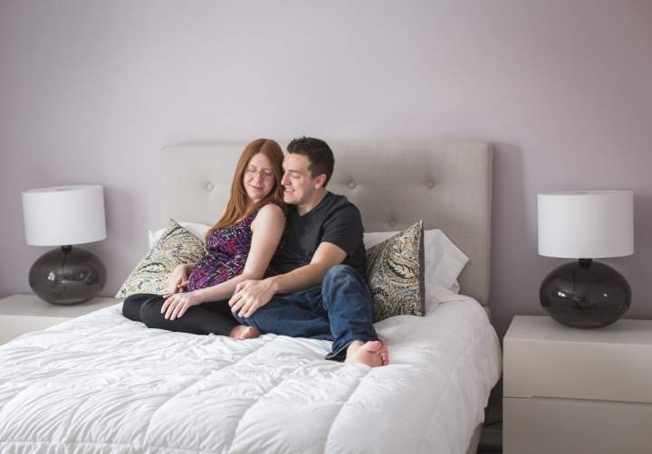 expecting couple snuggling on bed