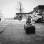 black and white lifestyle image of young boy trying to pull hockey bag in st.jacobs