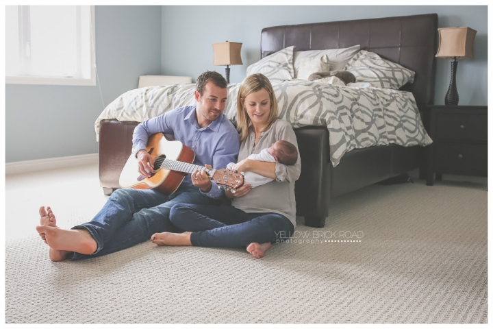 Mom and dad playing guitar to newborn daughter