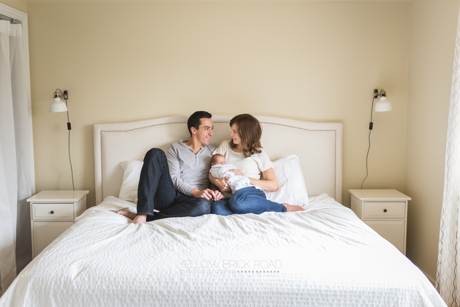parents with new son on their master bed during newborn lifestyle session