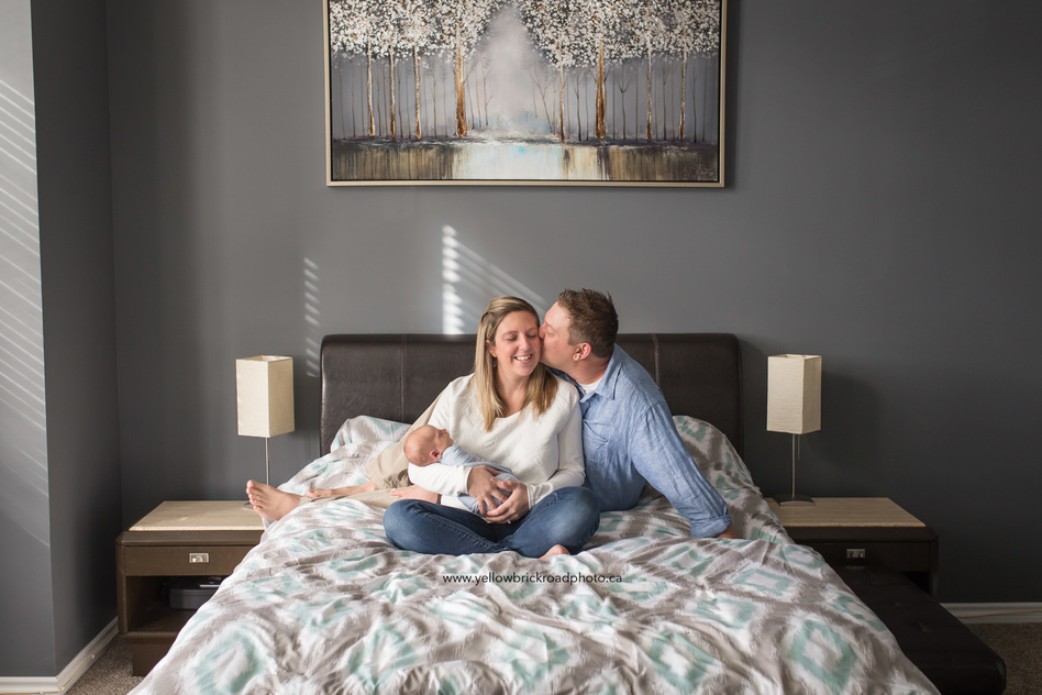 Guelph Newborn Photographer capturing family on the bed