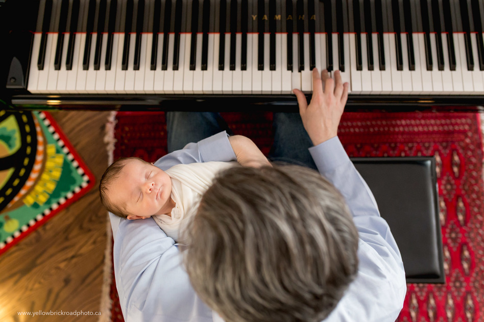 Toronto Newborn Lifestyle Photographer Dad playing piano with newborn