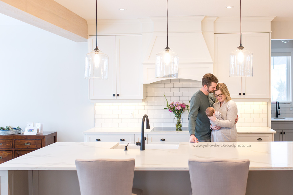Newborn Lifestyle Photographer Guelph Parents holding baby in white kitchen